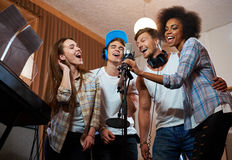 Multiracial music band performing in a recording studio Royalty Free Stock Images