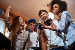 Multiracial music band performing in a recording studio Royalty Free Stock Photos