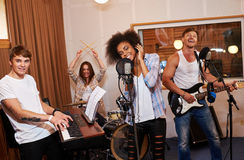 Multiracial music band performing in a recording studio.  Royalty Free Stock Image