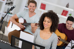 Multiracial music band performing in recording studio. Multiracial music band performing in a recording studio Royalty Free Stock Image