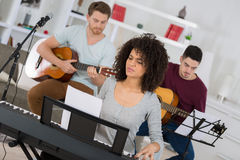 Multiracial music band performing in recording studio Royalty Free Stock Photos