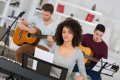 Multiracial music band performing in recording studio. Multiracial music band performing in a recording studio stock photo