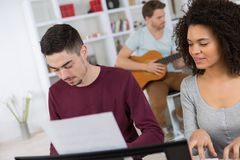 Multiracial music band performing in recording studio. Multiracial music band performing in a recording studio stock photography