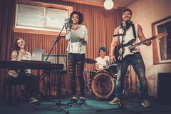 Multiracial music band in a studio. Multiracial music band performing in a recording studio Stock Image