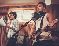 Multiracial music band in a studio. Multiracial music band performing in a recording studio Royalty Free Stock Photo