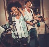 Multiracial music band in a studio. Multiracial music band performing in a recording studio Stock Photo