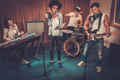 Multiracial music band in a studio. Multiracial music band performing in a recording studio Stock Images