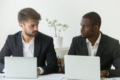 Multiracial office rivals looking at each other, rivalry at work royalty free stock photography