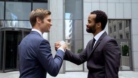 Multiracial partnery trząść ręki po tym jak pomyślna transakcja, praca zespołowa w rozpoczęciu fotografia stock