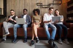 Multiracial people addicted to gadgets not talking to each other. Multiracial young people obsessed with smartphones and laptops, sitting in row not talking to stock photo