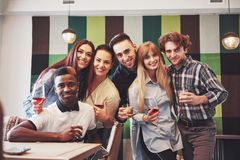 Multiracial people having fun at cafe taking a selfie with mobile phone. Group of young friends sitting at restaurant.  Stock Photo