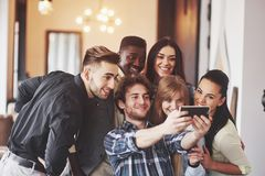Multiracial people having fun at cafe taking a selfie with mobile phone. Group of young friends sitting at restaurant. Taking self portrait with smart phone Royalty Free Stock Photography