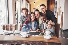 Multiracial people having fun at cafe taking a selfie with mobile phone. Group of young friends sitting at restaurant.  Royalty Free Stock Image