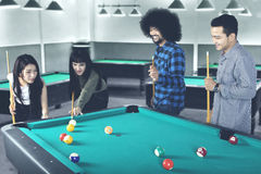 Multiracial people playing billiard Royalty Free Stock Images