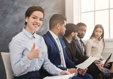Multiracial people waiting in queue preparing for job interview. Cheerful women showing thumb up, multiethnic people waiting in queue. preparing for job stock photo