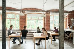 Multiracial people working and talking in modern co-working spac. Multiracial people work in modern co-working center interior, diverse employees collaborate stock photo