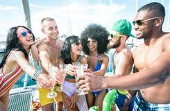 Multiracial przyjaciele ma zabawę pije szampańskiego wino przy żagiel łodzi przyjęciem - przyjaźni pojęcie z młodymi wielorasowym zdjęcia royalty free
