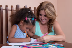 Multiracial small girl and her mother drawing with color pencils Royalty Free Stock Photography
