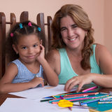 Multiracial small girl and her mother drawing with color pencils Royalty Free Stock Image