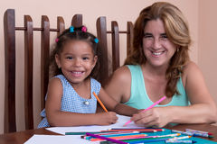 Multiracial small girl and her mother drawing with color pencils Stock Photography