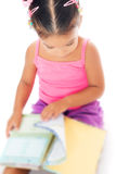 Multiracial small girl reading a book. With a shallow depth of field Stock Photography
