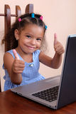Multiracial small girl using a laptop computer Stock Image