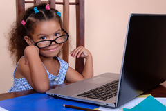 Multiracial small girl wearing glasses and using a laptop comput. Funny multiracial small girl wearing glasses and using a laptop computer at home royalty free stock image