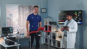 Multiracial sport professional performing stress test while the athlete walking on treadmill. Computer supervises whole test process. In Scientific Sports stock footage
