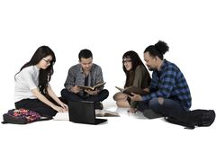 Multiracial student studying on the floor. Group of multiracial college student studying together while sitting on the floor, isolated on white background Stock Photo