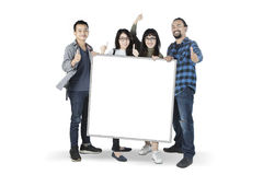 Multiracial students with blank board Royalty Free Stock Image