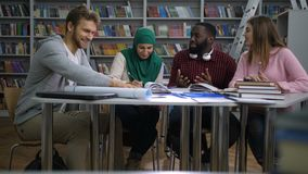 Multiracial students doing group study in library