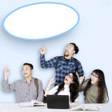 Multiracial students and empty speech bubble. Group of multiracial students thinking idea and pointing at an empty speech bubble with laptop on the table Stock Photography