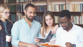 Multiracial students having fun in library while preparing for exams. stock video