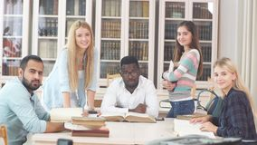 Multiracial students having fun in library while preparing for exams stock footage