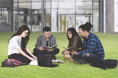 Multiracial students studying at park. Group of multiracial students studying together while discussing on the park with laptop and books Royalty Free Stock Image