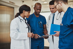 Multiracial team of doctors discussing a patient. Standing grouped in the foyer looking at a tablet computer, close up view stock photos