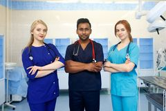 Multiracial team of young doctors in a hospital standing in a operating room. Multiracial team of doctors in a hospital standing in a corridor ready to make a Stock Photo