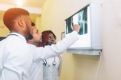 Multiracial team of young doctors looking at x-ray healthcare, medical and radiology concept. Healthcare, medical and radiology concept - three doctors looking Stock Photos