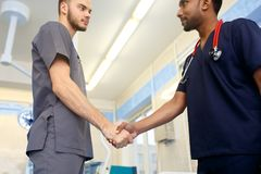Two young Doctors shaking hands to each other. Multiracial team of young doctors. Multiracial team of young doctors. Two young doctors shaking hands to each Royalty Free Stock Photos