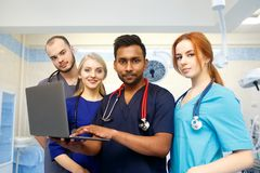 Multiracial team of young doctors working on laptop computer in medical office. Team of doctors working on laptop computer in medical office Royalty Free Stock Image