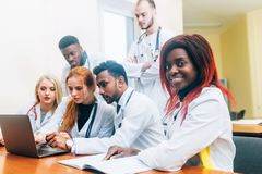Multiracial team of young doctors working on laptop computer in medical office. Team of doctors working on laptop computer in medical office Stock Photos