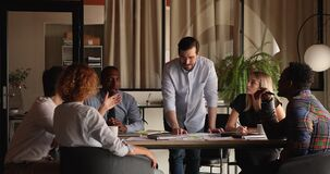 Multiracial teammates brainstorming during morning briefing in modern office boardroom