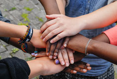 Multiracial teen friends joining hands together in cooperation Royalty Free Stock Photography