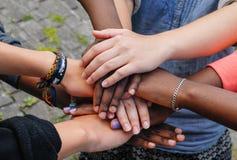 Multiracial teen friends joining hands together in cooperation. Multiracial teenagers joining hands together in cooperation royalty free stock photography