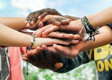 Multiracial teen friends joining hands together in cooperation. Multiracial teenagers joining hands together in cooperation royalty free stock image