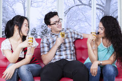 Multiracial teenager drinking beer on sofa Stock Photography