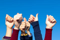 Multiracial Thumbs Up. Against Blue Sky Stock Image