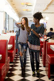 Multiracial women in the diner. Two young women socializing in the diner Royalty Free Stock Photography