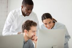 Multiracial work group watching funny video at computer in offic. Multiracial young professionals team watching funny video at personal computer, workers reading stock image