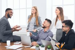 Multiracial work team tlking during coffee break. Multiracial work team talking during coffee break at meeting in office stock images